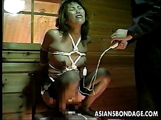 Asian freak on a chair straddles a sex toy
